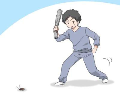 丸めた新聞紙でゴキブリを倒そうとしている男性