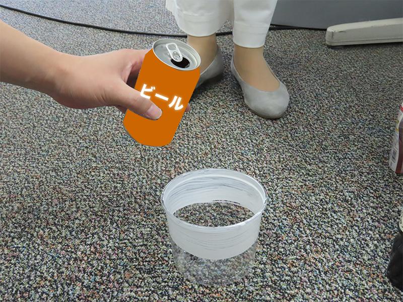 プラスチックのケースに入ったクロゴキブリにビールをかける様子