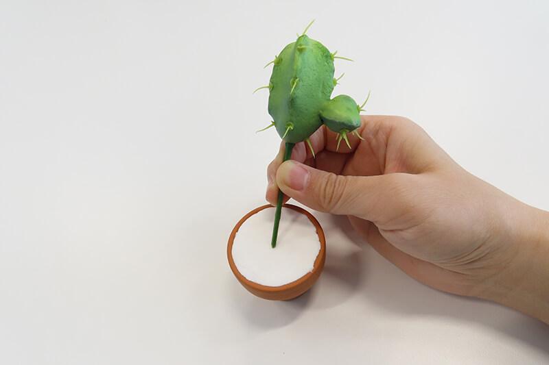ホウ酸団子を敷き詰めた「テラコッタ ミニモ 4cm」に造花をさす様子