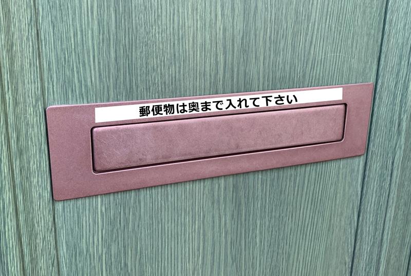 郵便物を奥まで差し込んでくださいと書いたシールを郵便受けにはった玄関ドア