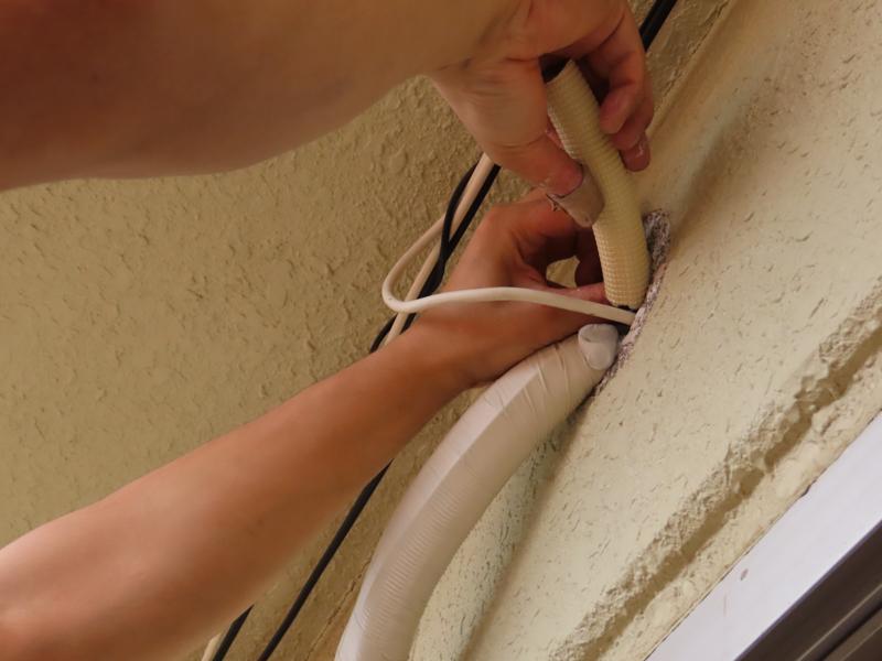 エアコンの配管を通すために開けた壁の穴をパテで塞ぐ様子