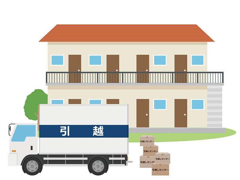 集合住宅の前に止まった引っ越しトラックと荷物