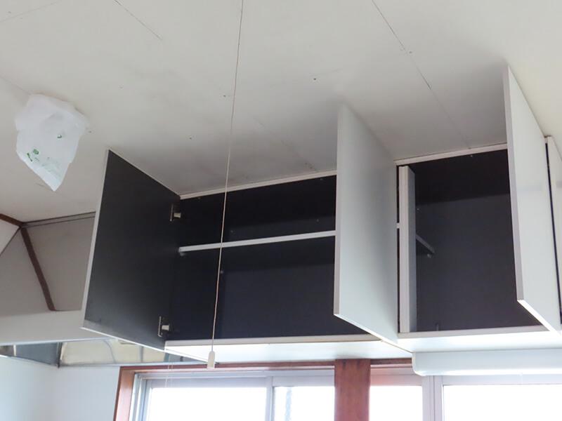 扉が開かれた台所の上部収納棚