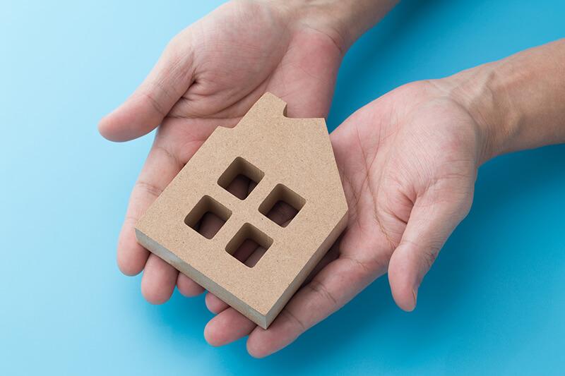 両手に載せた、家の形をした木製オブジェ