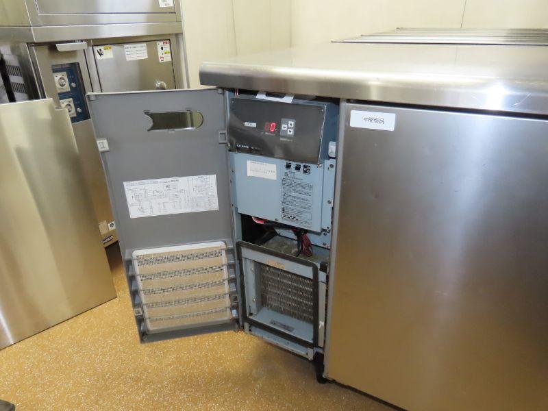 ダスキンの研修センターの厨房にある業務用冷蔵庫のモーターの扉を開けている様子