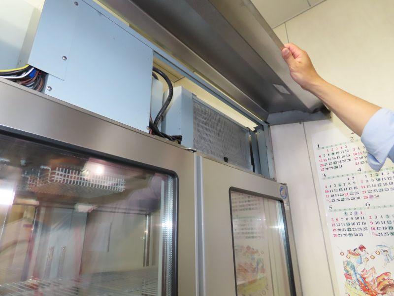 ダスキンの研修センターの厨房にある業務用冷蔵庫の電熱線がある場所の扉を開けている様子