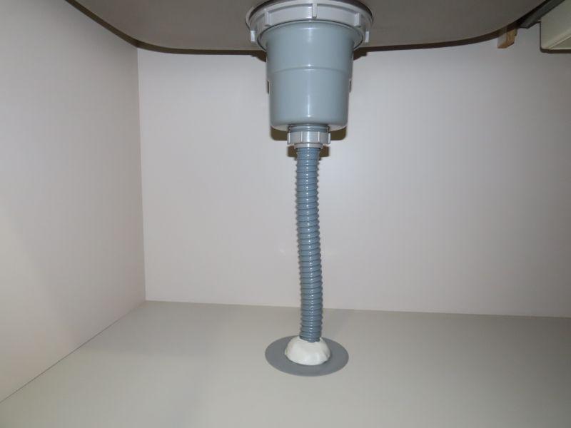 ダスキンの研修センターのにある家庭用の洗面所を再現したブースで排水管を確認している様子