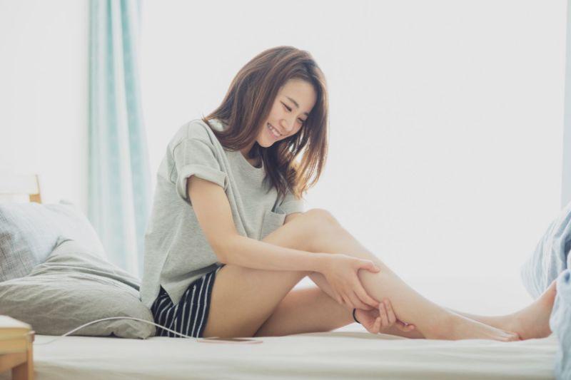 """""""ベッドの上で自分のふくらはぎを揉む女性の写真"""""""